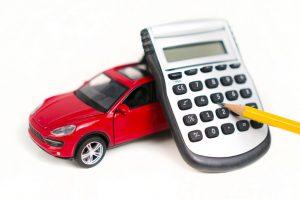Model červeného auta a kalkulačka s povinným zmluvným poistením